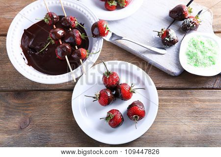 Served table with delicious strawberries in chocolate on wooden background