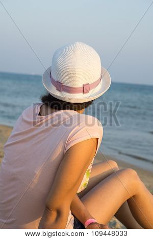 Girl Brunette In White Hat Looking At Sea While Sitting On Beach