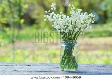 Lily Of The Valley In Bottle On Grey Wooden Background, Outdoors