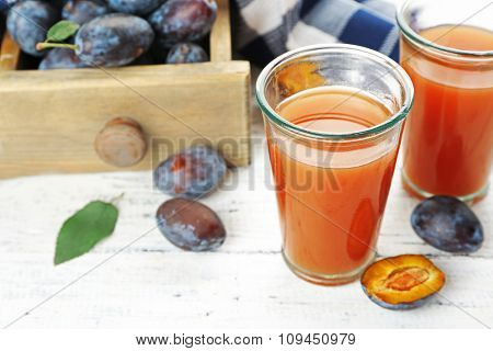 Plum Juice in glasses with fresh fruits