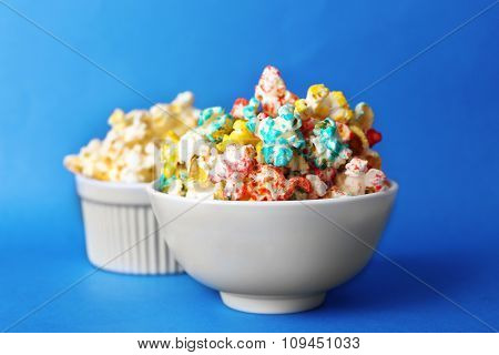 Sweet colourful and salted popcorn in bowls on blue background