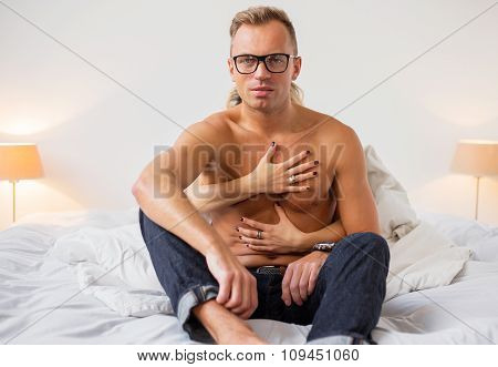 Sexy man in bedroom wrapped in woman's arms