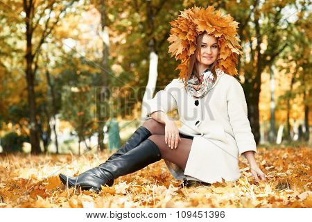 girl sitting on leaves in sunny autumn city park