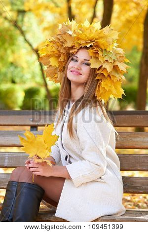 girl portrait with leaves on head in autumn city park