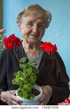 An elderly woman stands on the balcony with homemade flowers in hand.