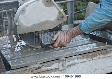 Senior Worker Cutting Tile With A Stone Saw
