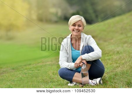 Senior woman relaxing outside, sit in park