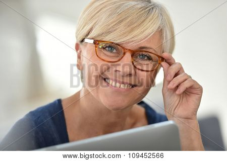 Senior woman with eyeglasses browsing on digital tablet