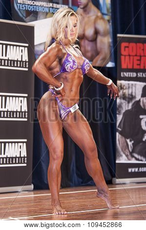 Female Bodybuilder Posing On Stage In Pink Bikini