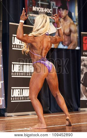 Female Bodybuilder In Back Double Biceps Pose And Pink Bikini