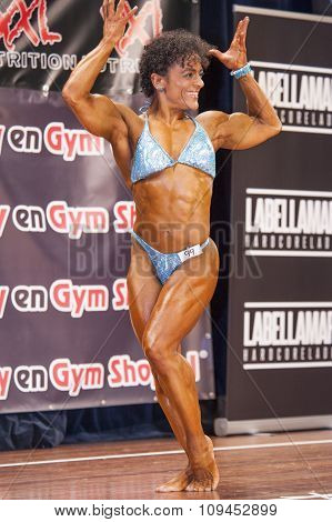 Female Bodybuilder In Double Biceps Pose And Blue Bikini