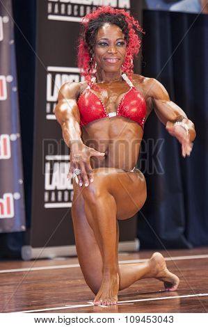 Female Bodybuilder In Red Bikini Posing On Stage