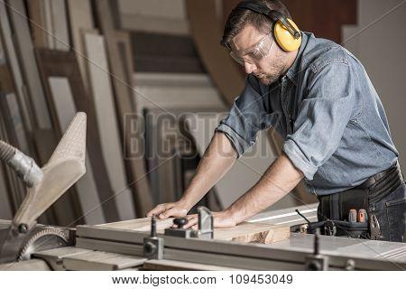 Carpenter Cutting Wood On Workbench