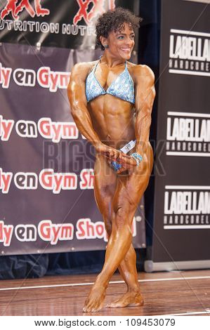 Female Bodybuilder In Triceps Pose And Blue Bikini