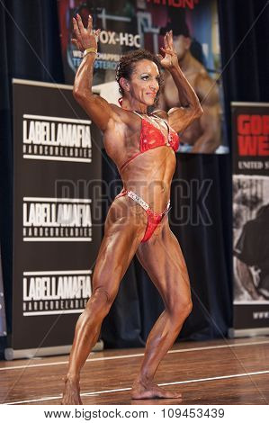 Female Bodybuilder In Double Biceps Pose And Red Bikini