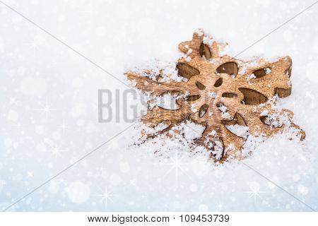 Snowflake on white snowy background with bokeh effect