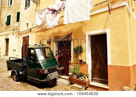 Typical south Italy view with old obsolete building, washing linen and cargo moped. The spirit of south Mediterranean Italy. Image toned.
