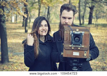 Photographer hipster takes photo with retro camera outdoor, image toned and noise added.