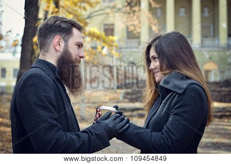 Fashion portrait of young couple drinking coffee in autumn park outdoor, image toned and noise added. Hipster man with beard and moustache embracing his beautiful happy smiling girlfriend outside.
