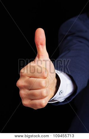 Hand of man holding thumb up on black background