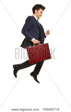 Happy businessman jumping into the air with a briefcase
