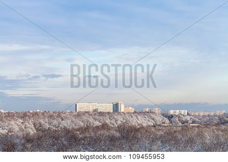 Blue Clouds In Blue Sky Over Snow Forest And Town