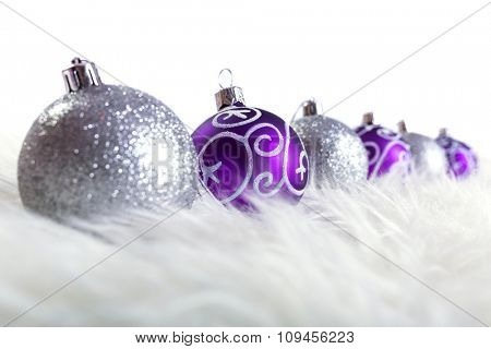 Purple and silver christmas baubles over white background