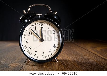 Alarm clock showing almost midnight. New year symbol.