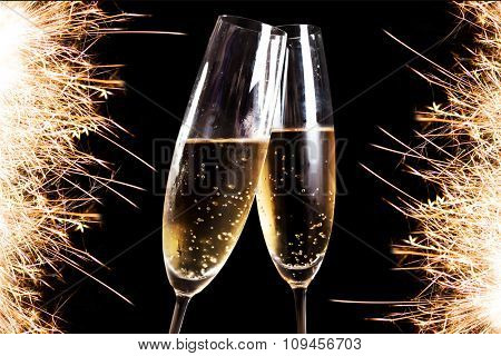 Two flutes of champagne over fireworks display