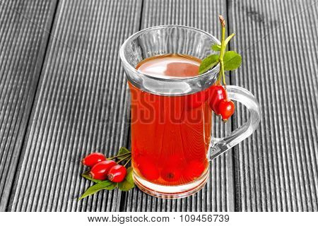 Monochrome image of a glass of tea with a red rose hip