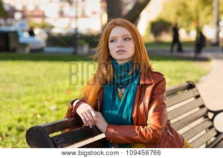 Young attractive pensive woman with beautiful red hair in leather jacket sitting on bench in the park