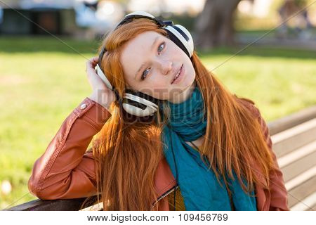 Portrait of relaxed charming young lady with beautiful long red hair enjoying music in headphones on bench in park