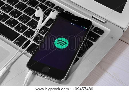 Iphone 5S On Laptop With Mobile Application For Spotify On The Screen