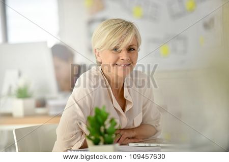 Senior businesswoman in office working on digital tablet