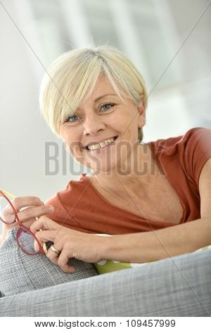 Cheerful senior woman sitting on couch at home