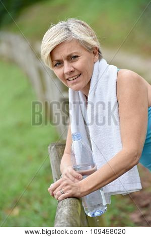 Portrait of athletic senior woman holding bottle of water