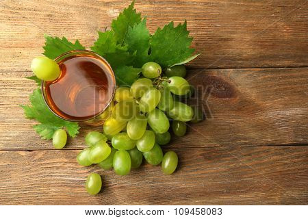 Glass of grape juice on wooden table, top view