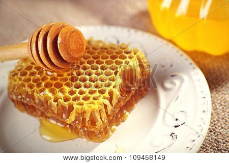 Honeycomb, dipper on white plate and pot of honey closeup