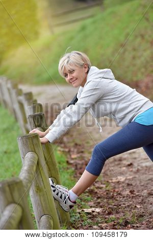 Senior woman stretching after exercising in natural landscape