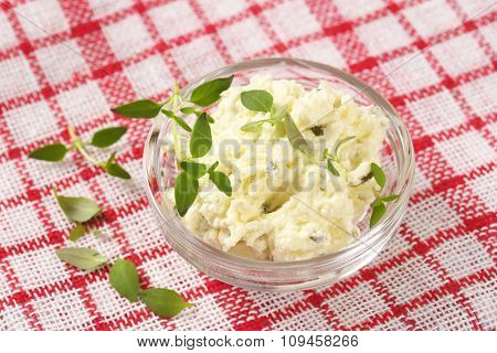 close up of homemade cheese spread with herbs in glass bowl