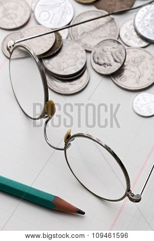 rimmed glasses and different coins on math paper