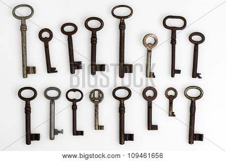 collection of old rusty keys on white