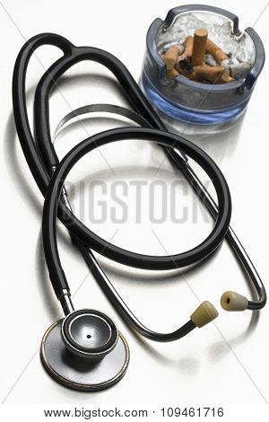 stethoscope and full ashtray on white