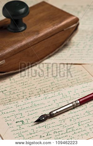 vintage nib pen on a written letter with a blotting pad in the back
