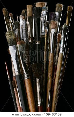bunch of painting brushes against black