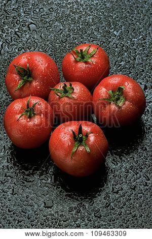 sprinkled ripe tomatoes on wet black surface