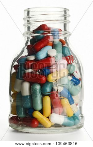 a jar filled with pills on white