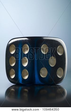 a transparent blue dice on bluish background