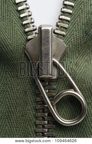 detail of a zipper on green fabric