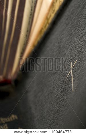 a detail of an old bible - shallow depth of field, focus on the cross